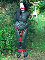 Leather brunette roped to the tree